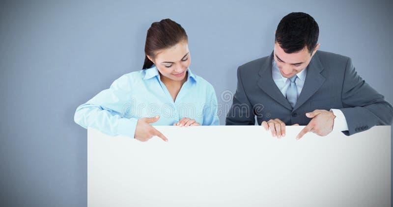 Составное изображение деловых партнеров смотря и указывая на знак они держат стоковая фотография