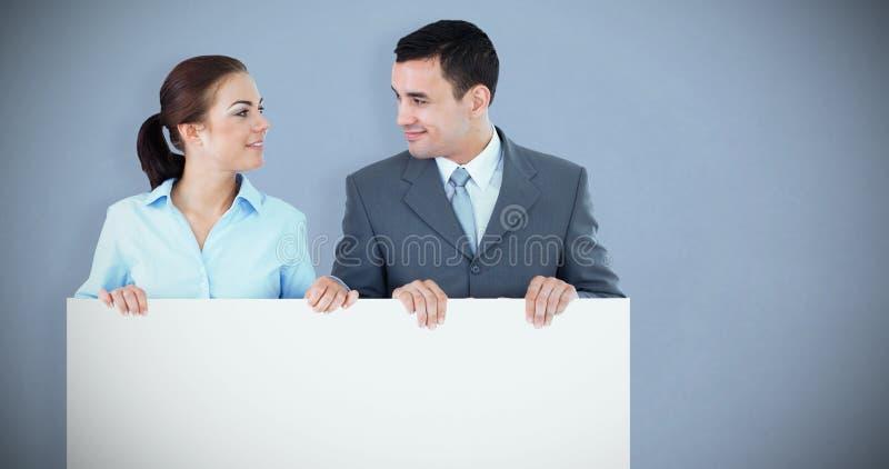 Составное изображение деловых партнеров смотря один другого пока держащ знак совместно стоковое изображение