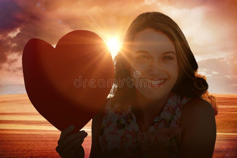 Составное изображение женщины держа карточку сердца и дуя поцелуй стоковые изображения rf
