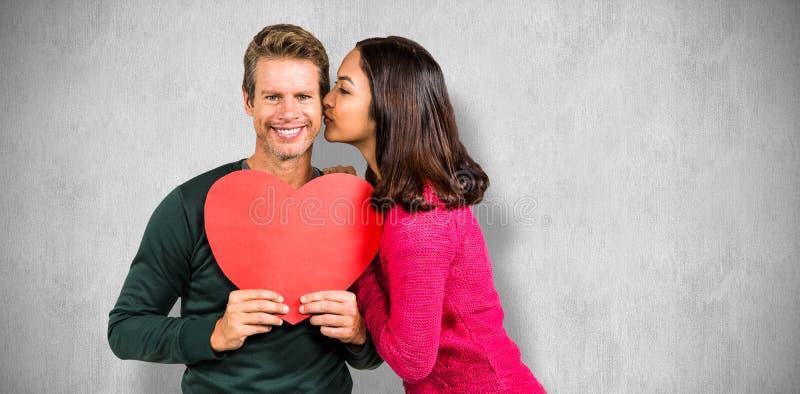Составное изображение женщины целуя парня с красной формой сердца стоковые фото