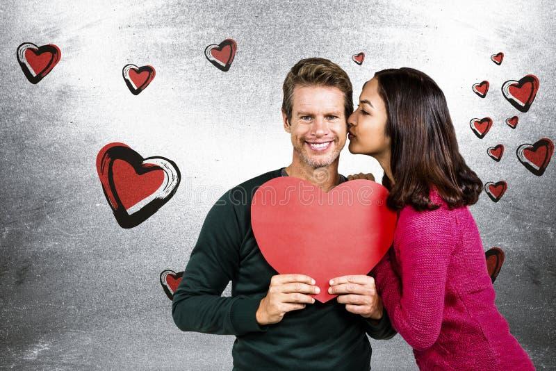 Составное изображение женщины целуя парня с красной формой сердца стоковое фото rf