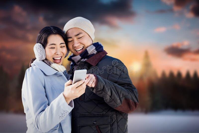 Составное изображение жизнерадостных пар смотря умный телефон стоковое фото rf