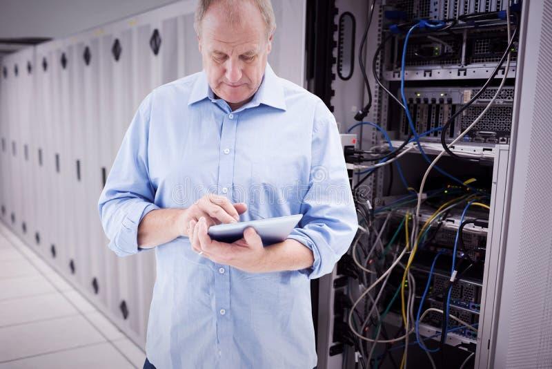Составное изображение зрелого человека используя его ПК таблетки стоковое фото rf