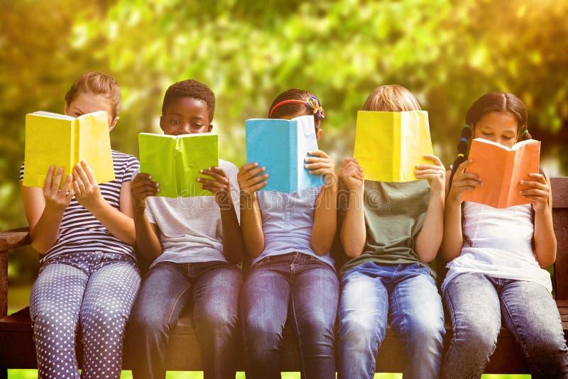 Составное изображение книг чтения детей на парке стоковое изображение
