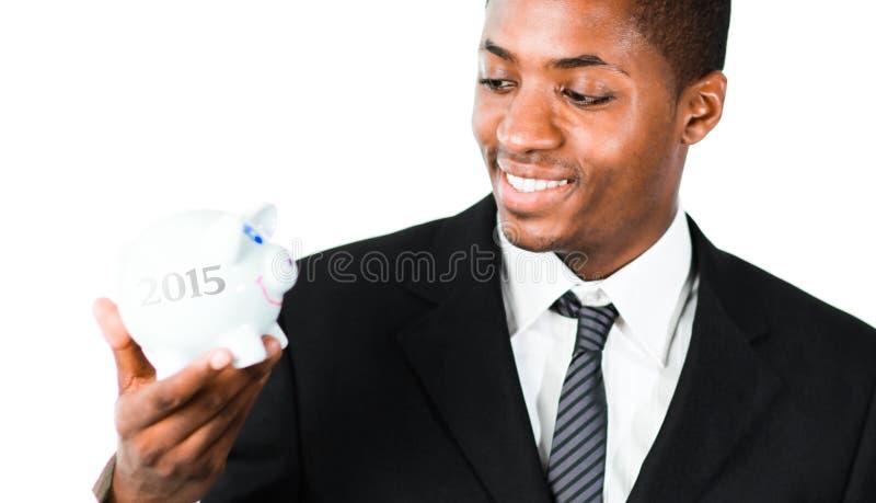 Составное изображение конца вверх молодого бизнесмена смотря копилку стоковое фото