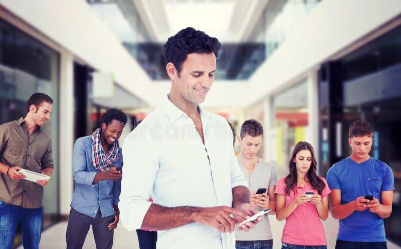 Составное изображение красивого человека используя умный телефон стоковая фотография