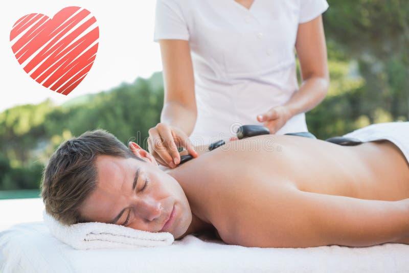 Составное изображение красивого человека получая горячий каменный poolside массажа стоковое изображение