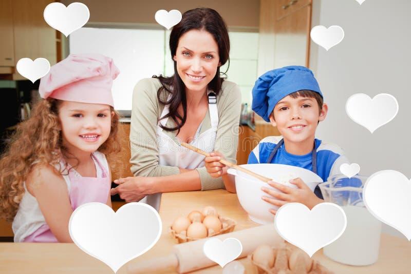 Составное изображение матери и ее детей подготавливая торт стоковое фото rf