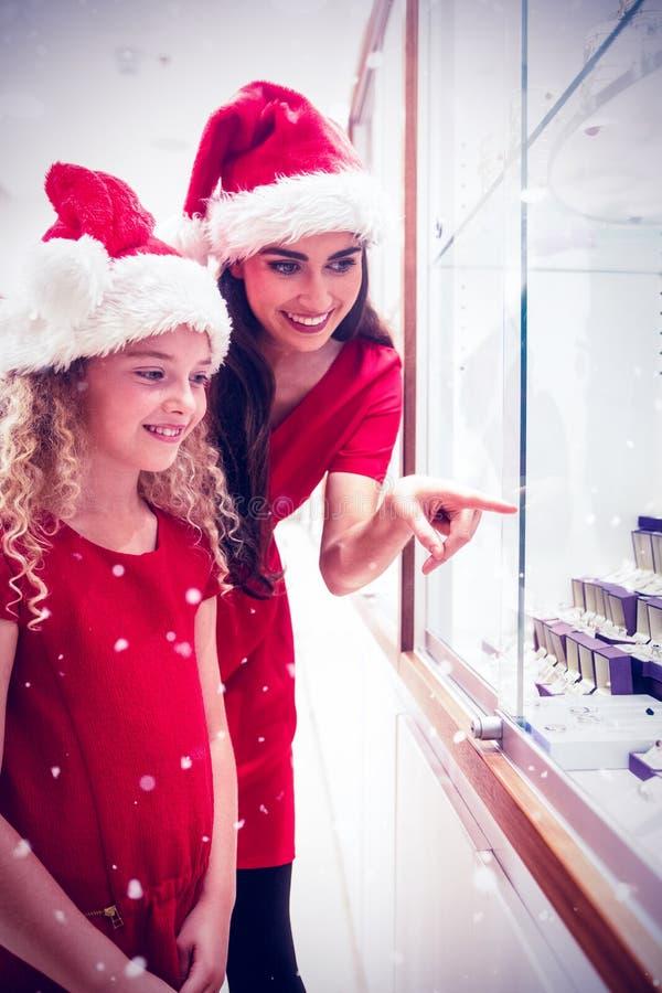 Составное изображение матери и дочери в одежде рождества смотря дисплей ювелирных изделий стоковое фото