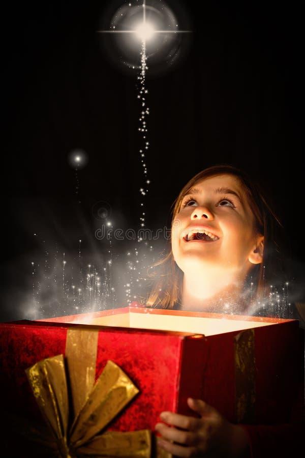 Составное изображение маленькой девочки раскрывая волшебный подарок рождества стоковые изображения rf