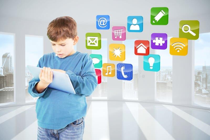 Составное изображение милого мальчика используя таблетку стоковые фото