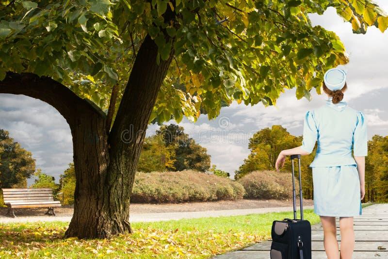 Составное изображение милой склонности стюардессы на чемодане стоковое фото