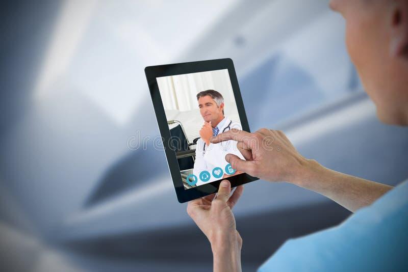 Составное изображение мужской медсестры используя цифровую таблетку стоковое фото rf