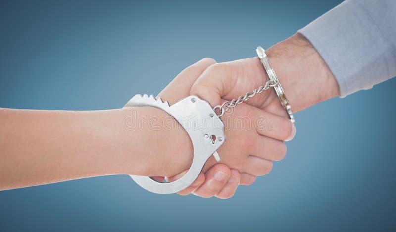 Составное изображение надеванных наручники бизнесменов тряся руки стоковое фото