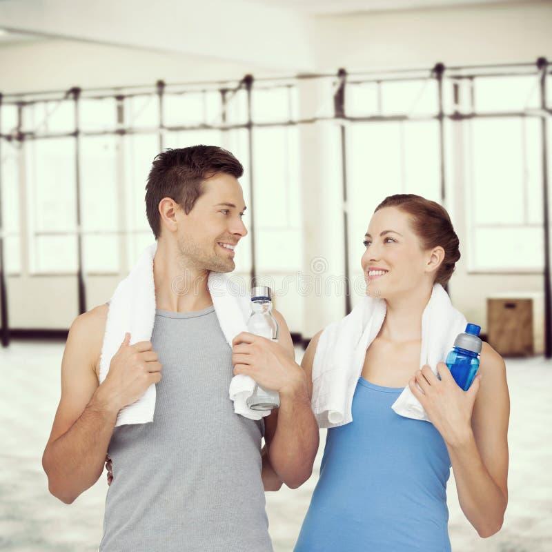 Составное изображение пар счастливой пригонки молодых с бутылками с водой стоковое изображение