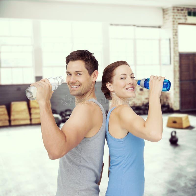 Составное изображение пар счастливой пригонки молодых с бутылками с водой стоковые изображения