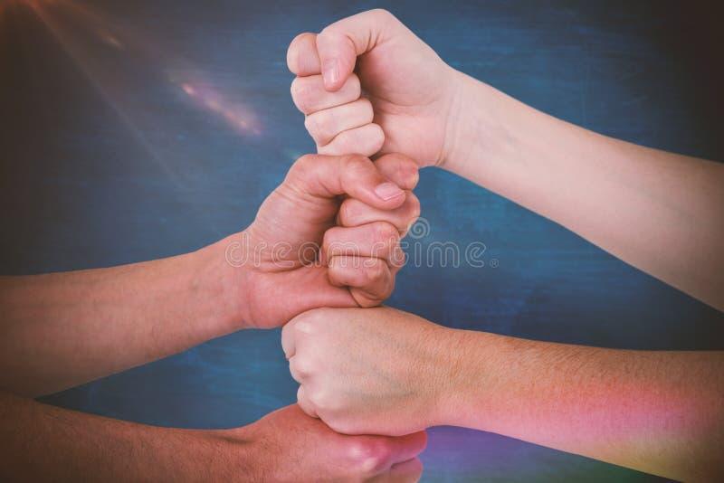 Составное изображение подрезанного изображения людей с штабелированными кулаками стоковое фото rf