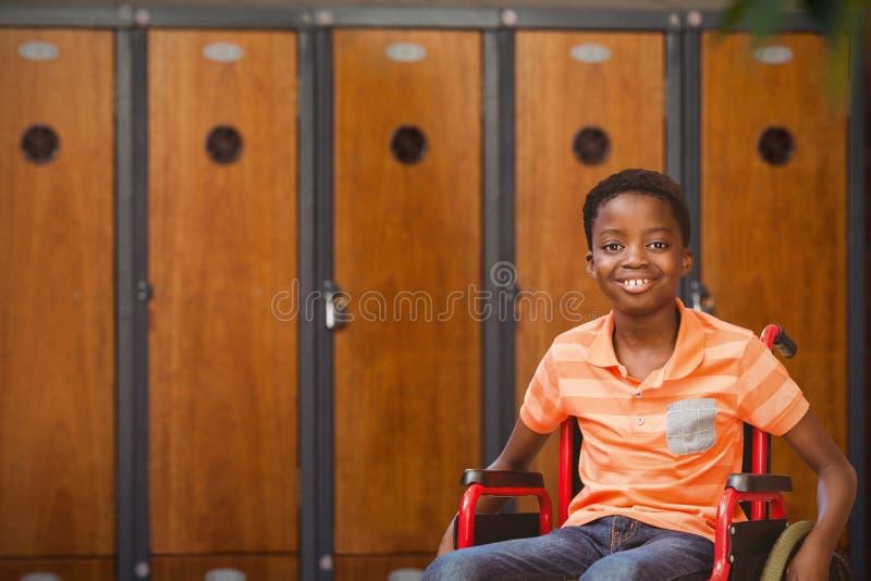 Составное изображение портрета мальчика сидя в кресло-коляске на библиотеке стоковое фото rf
