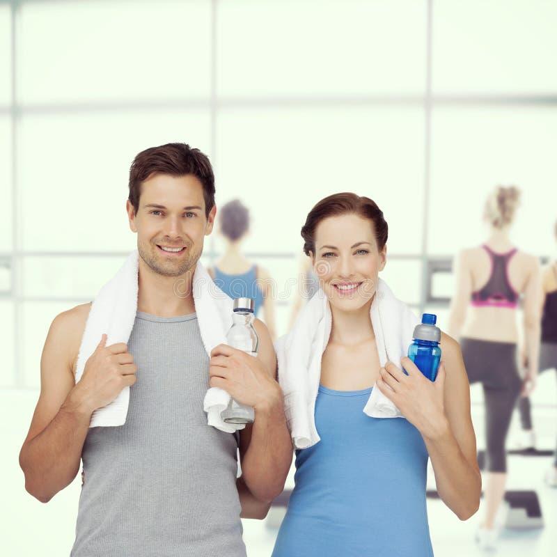 Составное изображение портрета счастливой пары пригонки с бутылками с водой стоковые изображения