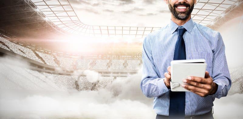 Составное изображение портрета усмехаясь бизнесмена используя планшет стоковое изображение rf