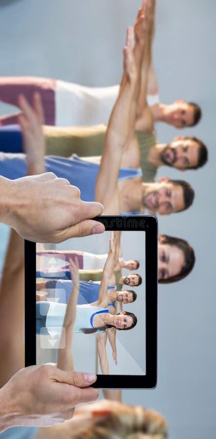 Составное изображение подрезанной руки держа цифровую таблетку стоковая фотография rf