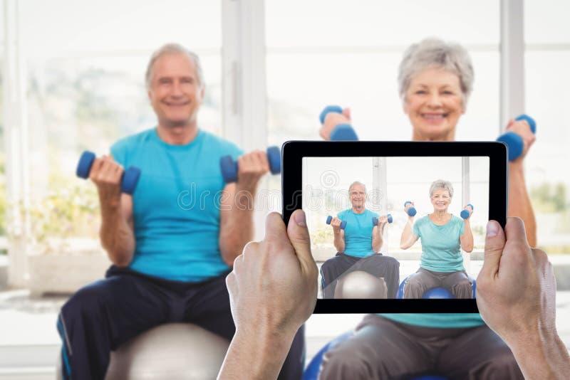 Составное изображение подрезанной руки держа цифровую таблетку стоковые изображения rf
