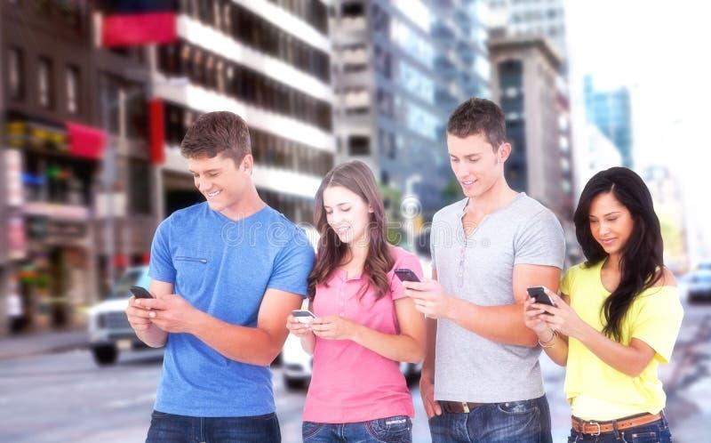 Составное изображение 4 друзей стоя к стороне немножко посылая отправляет СМС стоковое фото rf