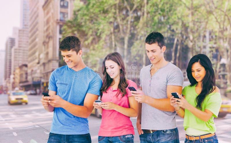 Составное изображение 4 друзей стоя к стороне немножко посылая отправляет СМС стоковое фото