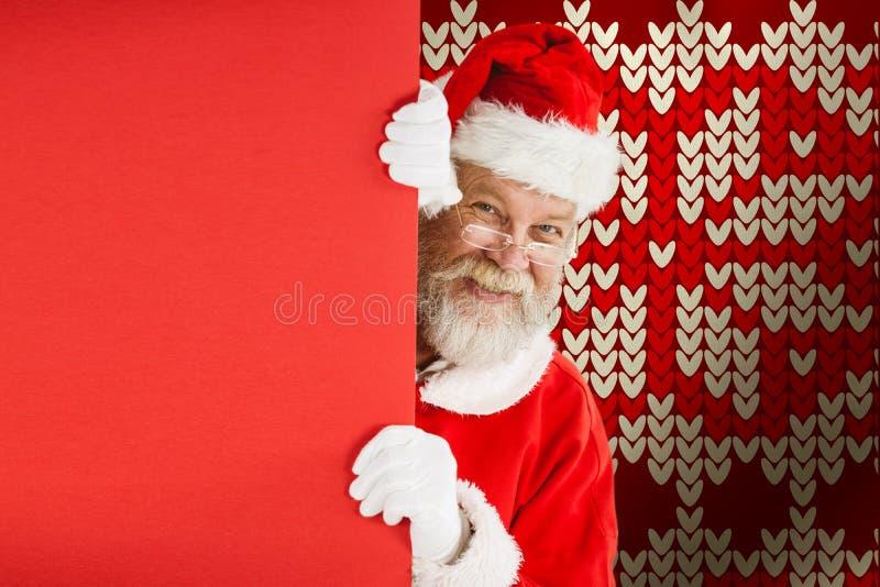 Составное изображение Санта Клауса peeking от красной доски стоковые изображения rf