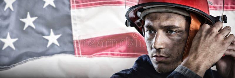Составное изображение серьезного пожарного кладя на шлем стоковая фотография rf