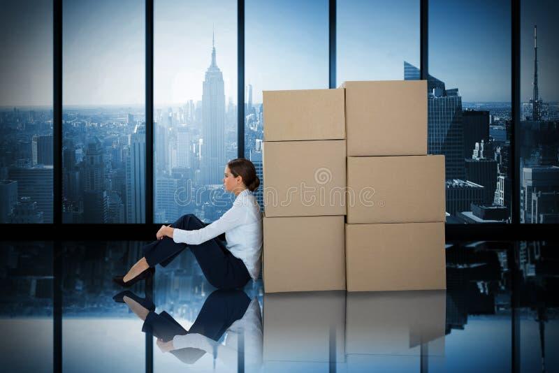 Составное изображение склонности коммерсантки на картонных коробках против белой предпосылки стоковое фото