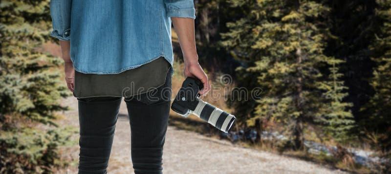 Составное изображение среднего раздела мужского фотографа держа цифровой фотокамера стоковые фото