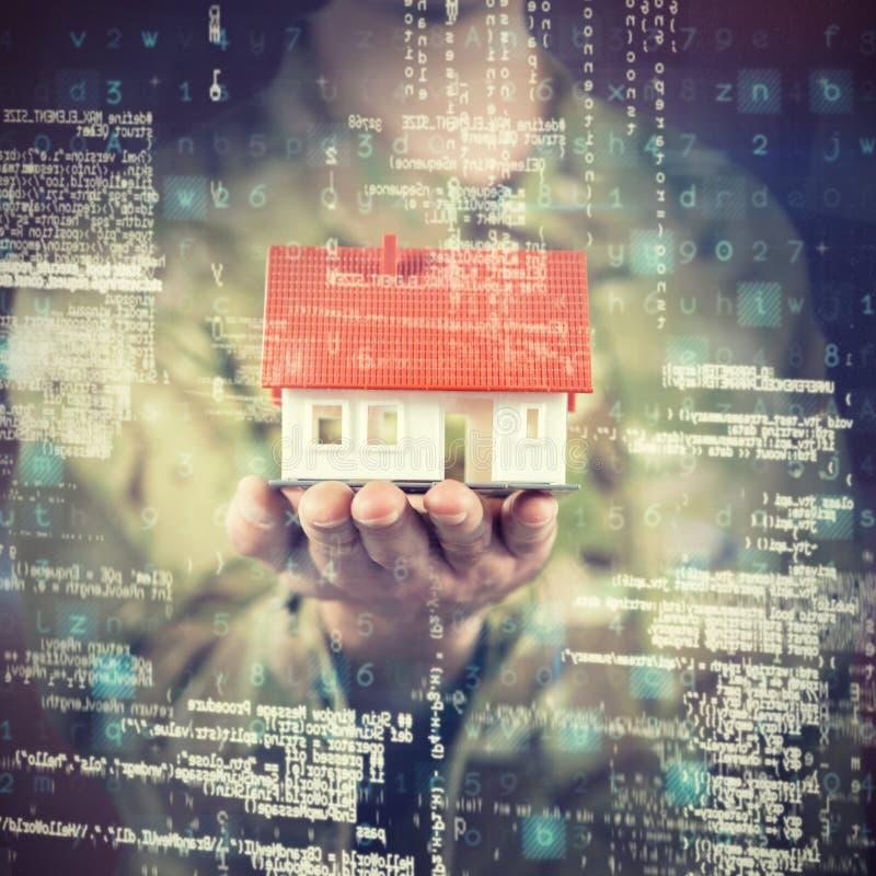 Составное изображение среднего раздела солдата держа модельный дом стоковое фото rf