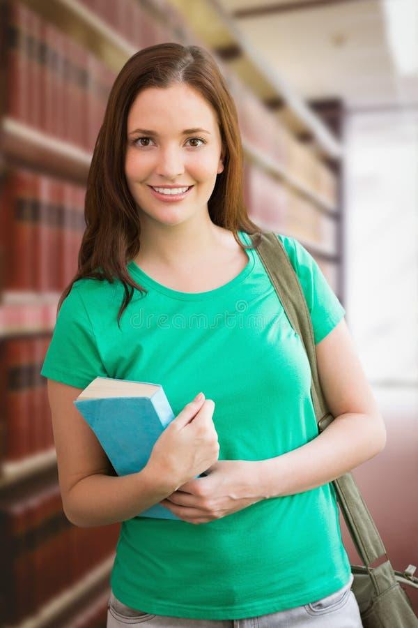 Составное изображение студента усмехаясь на камере в библиотеке стоковые фотографии rf