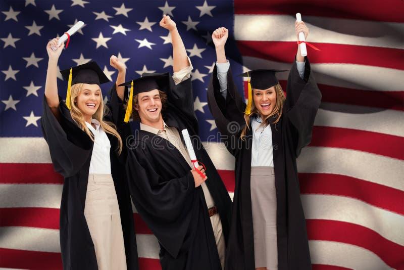 Составное изображение 3 студентов в постдипломной робе поднимая их оружия стоковое изображение rf
