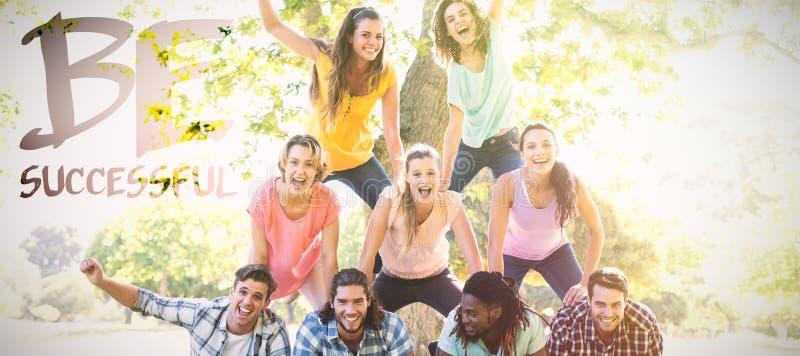 Составное изображение счастливых друзей в парке делая человеческую пирамиду стоковая фотография rf