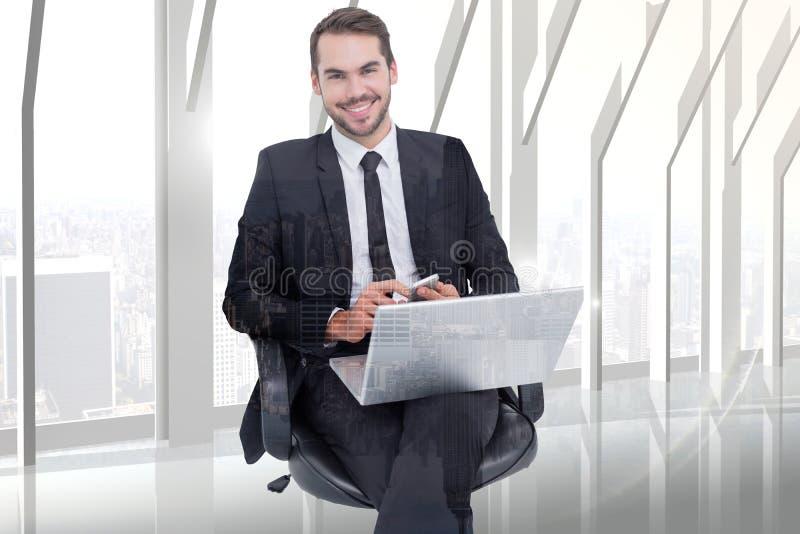 Составное изображение счастливого бизнесмена с компьтер-книжкой используя smartphone стоковое фото