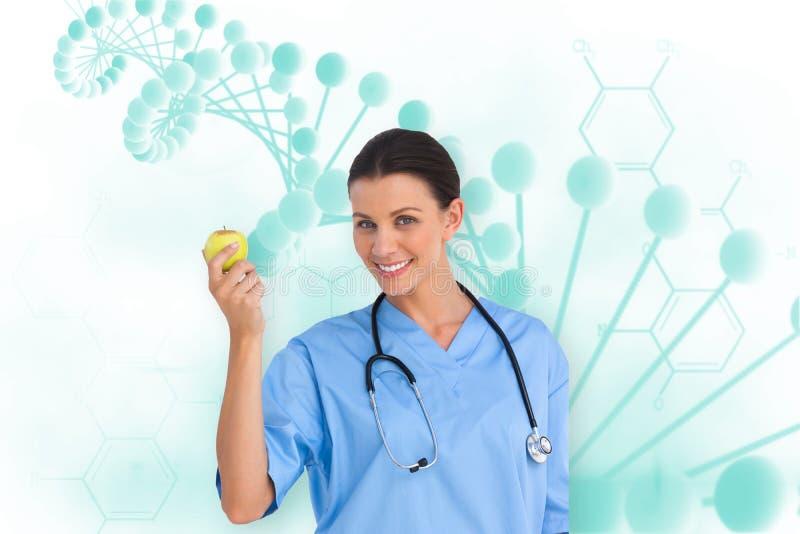 Составное изображение счастливого хирурга держа яблоко и усмехаясь на камере стоковое фото rf