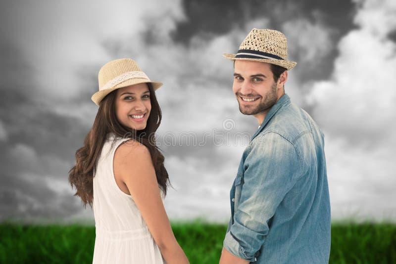 Составное изображение счастливых пар битника держа руки и усмехаясь на камере стоковое фото rf
