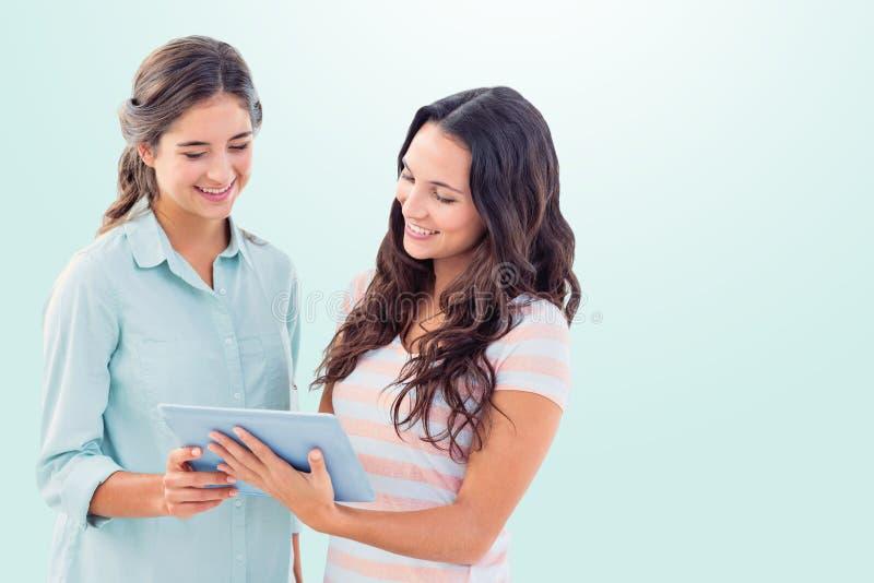 Составное изображение счастливых друзей используя таблетку стоковое фото