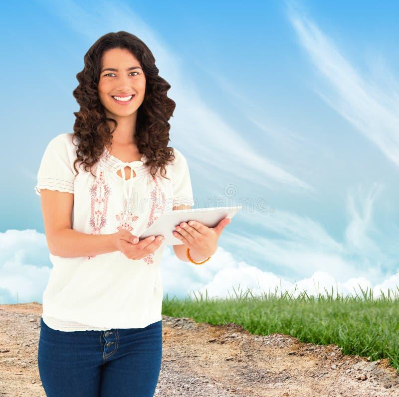 Составное изображение усмехаясь вскользь брюнет используя ее ПК таблетки стоковая фотография