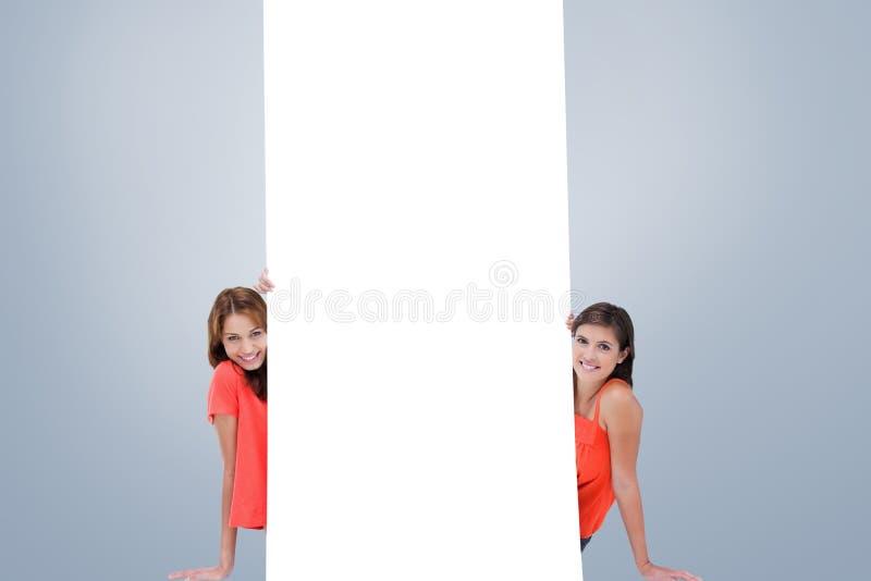 Составное изображение 2 усмехаясь девочка-подростков сидя за пустым плакатом стоковое изображение