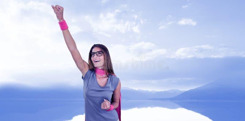 Составное изображение усмехаясь женщины в костюме супергероя при поднятая рука стоковая фотография