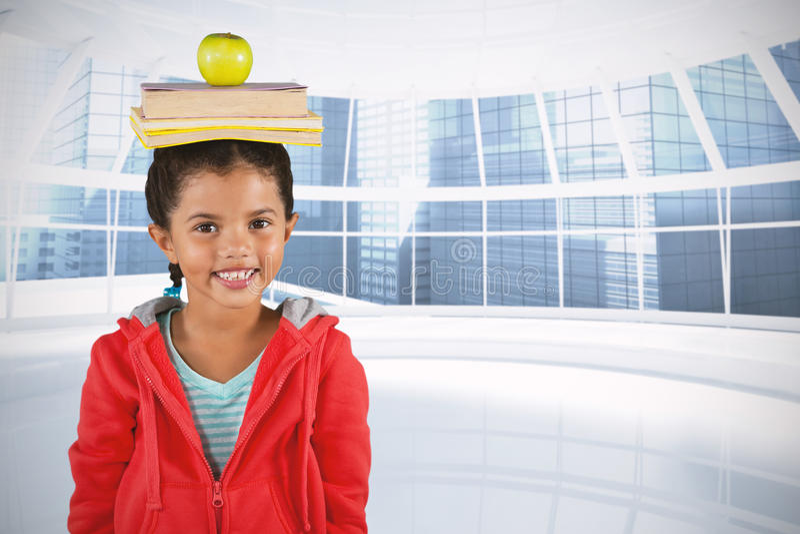 Составное изображение усмехаясь книг и яблока девушки балансируя на голове стоковые изображения