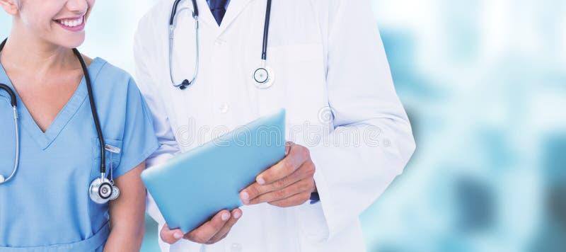Составное изображение усмехаясь мужского доктора при медсестра используя цифровую таблетку стоковое фото