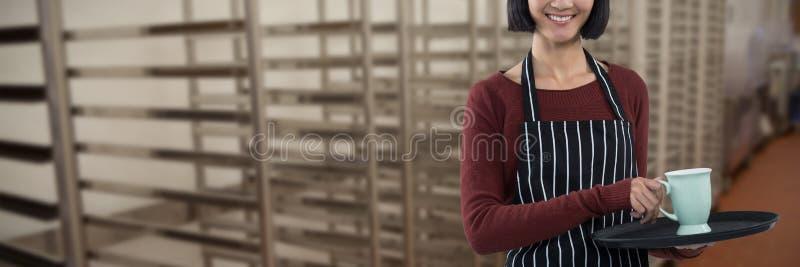 Составное изображение усмехаясь официантки держа поднос кофейной чашки против белой предпосылки стоковая фотография