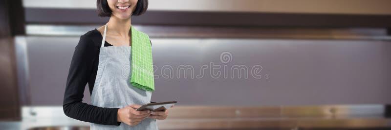 Составное изображение усмехаясь официантки держа цифровую таблетку против белой предпосылки стоковые изображения