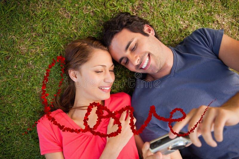 Составное изображение 2 усмехаясь друзей смотря фото на камере иллюстрация штока