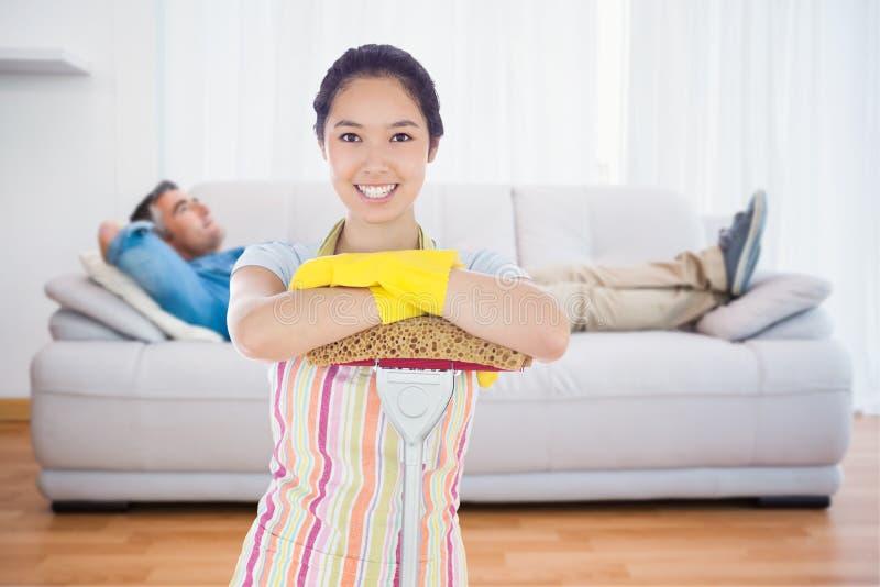 Составное изображение усмехаясь склонности женщины на mop стоковые фото