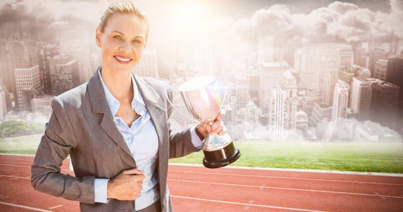 Составное изображение успешной коммерсантки держа трофей стоковое фото